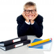Bespectacled boy posing with files on his desk — Stockfoto