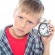 Stock Photo: Confused young kid holding time piece close to his ear