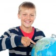 Cute little boy pointing out a continent on the globe — Stock Photo