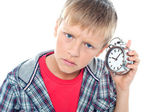 Confused young kid holding time piece close to his ear — Stock Photo