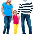 Sweet little kid standing in between her parents — Stock Photo