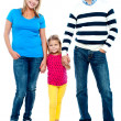 Sweet little kid standing in between her parents — Stock Photo #14150937
