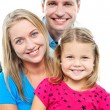 Parents posing with cute smiling daughter — Stock Photo