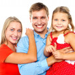 Cheerful family of three facing camera and smiling — Stock Photo