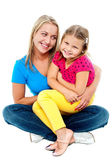 Cute daughter sitting in mother's lap — Stock Photo
