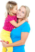 Fashionable young kid kissing her mother — Stock Photo