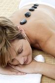 Bonita mujer disfrutando de terapia con piedras caliente — Foto de Stock