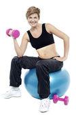 Woman seated on fitness ball doing dumbbells — ストック写真