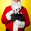 Cheerful Kris Kringle posing with clapperboard — Stock Photo