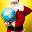 Foto Stock: Father Christmas showing his country on globe