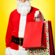 Stock Photo: Joyous Santposing with colorful shopping bags