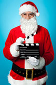 Bespectacled Santa holding a clapperboard — Stock Photo
