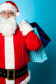 Saint Nicholas carrying colorful shopping bags — Stock Photo