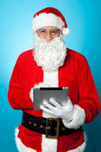 Modern Santa using digital touch screen device — Stock Photo