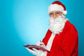 A thoroughly modern Santa claus checks his list on clipboard — Stock Photo