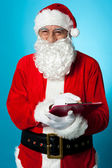 Santa Claus making his list of the good children — Stock Photo