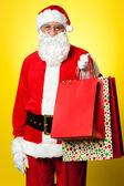 Joyous Santa posing with colorful shopping bags — Stock Photo