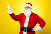 Cheerful Santa pointing away. Copy space concept. — Stock Photo