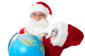 Expressionistic Santa pointing at north pole on globe — Stock Photo