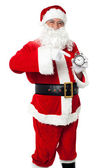 Santa pointing at an antique time piece — Stock Photo