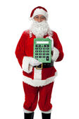 Old man dressed as Santa showing a large green calculator — Stock Photo