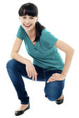Good looking female model in squatting posture — Stock Photo