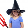 Pretty girl in witches hat holding devils pitchfork — Stock Photo