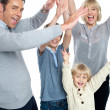 Jubilant family celebrating and partying indoors - Stock Photo