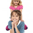 Adorable sister sitting on her brothers back — Stock Photo