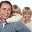 Fun loving family of three, girl piggybacking her father. — Stock Photo #16038191