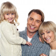 Cheerful family of three posing for camera — Stock Photo #16038205