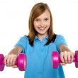 Adorable teen holding dumbbells in her outstretched arms — Stock Photo