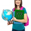 Smiling female student holding a calculator and globe — Stock Photo #16896889