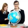 Teacher and student viewing globe in geography classroom — Stock Photo
