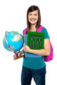 Smiling female student holding a calculator and globe — Stock Photo