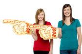 Cheerful fans pointing the big foam hand sideways — Stock Photo