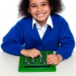 Stock Photo: Africelementary school kid using calculator