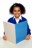 Uśmiechający się szkoły dziewczyna nauki tygodniowego przydziału — Zdjęcie stockowe