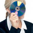 Corporate lady looking through compact disc hole — Stock Photo #18254019