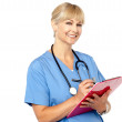 Physician with clipboard smiling at camera — Stock Photo