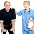 Stock Photo: Cheerful doctor encouraging her patient to walk with crutches