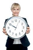 Business executive displaying big wall clock — Stock Photo