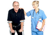 Cheerful doctor encouraging her patient to walk with crutches — Stock Photo