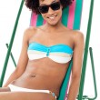 Sexy bikini model seated on a deckchair — Stock Photo