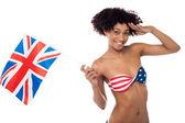 Hot American bikini model saluting and waving UK flag — Stock Photo