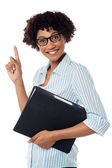 Young secretary holding file and pointing upwards — Stock Photo