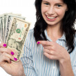 Happy woman holdng and pointing towards dollar notes — Stock Photo #19564211