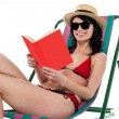 Enticing bikini model on a deckchair reading a book — Stock Photo