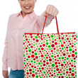Stock Photo: Cheerful blonde girl holding shopping bag in outstretched arm