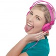 Woman with headphones on sticking her pierced tongue out — Stock Photo #19565981